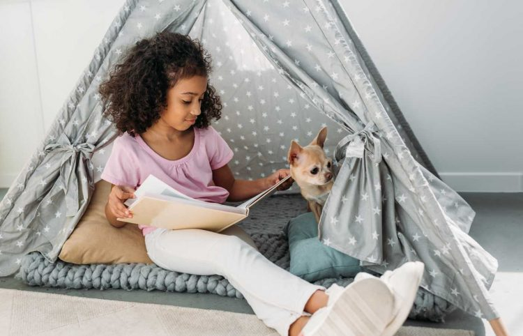 african kid reading a book with chihuahua dog inside a teepee at home